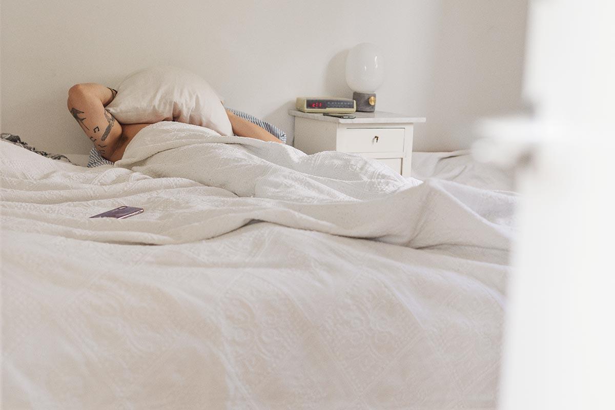 ungt menneske ligger i sengen